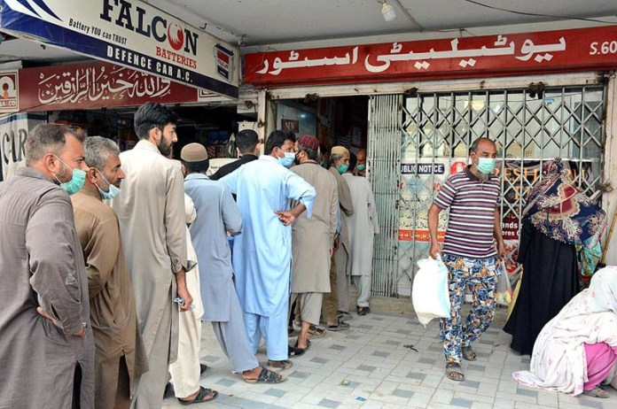 KARACHI: October 28 - People standing in queue at utility store for purchase flour bags on subsidized rates in Provincial Capital. APP Photo by M Saeed Qureshi