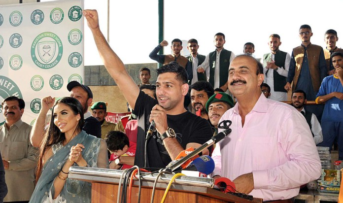 ISLAMABAD: October 03 - World Champion International Boxer British Pakistani Amir Khan and his wife visits Pakistan Sweet Home and distribute gifts and announce to become ambassador of PSH. APP photo by Saeed-ul-Mulk