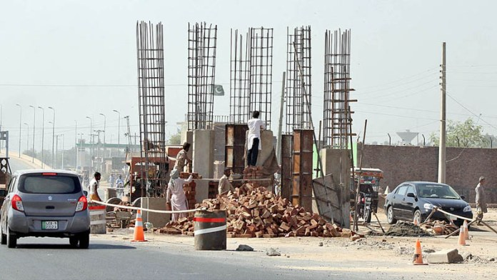 MULTAN: October 17 – Labourer busy in construction work of entrance gate of city near Nag Shah chowk. APP photo by Tanveer Bukhari