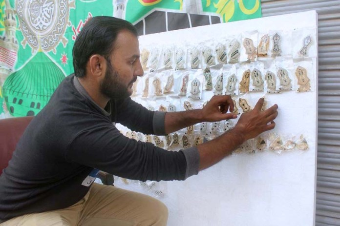 MULTAN: October 29 – A vendor busy in displaying badges related Eid-Milad Un Nabi celebrations to attract the customer at his roadside setup. APP photo by Tanveer Bukhari
