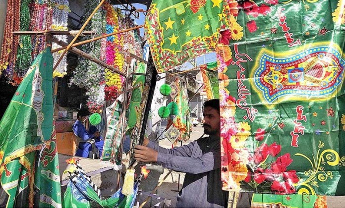 LARKANA: October 21 – A vendor displaying decorative flags and other stuff to attract the customers in connection with Eid-e-Milad-un-Nabi (SAWW) celebrations. APP photo by Nadeem Akhtar