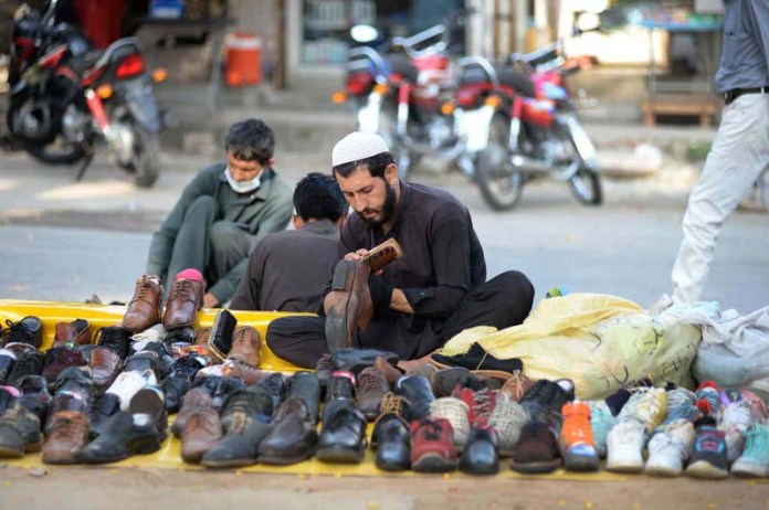 ISLAMABAD: October 22 - A vendor displaying used shoes to attract the customers at Aabpara market. APP photo by Irshad Sheikh