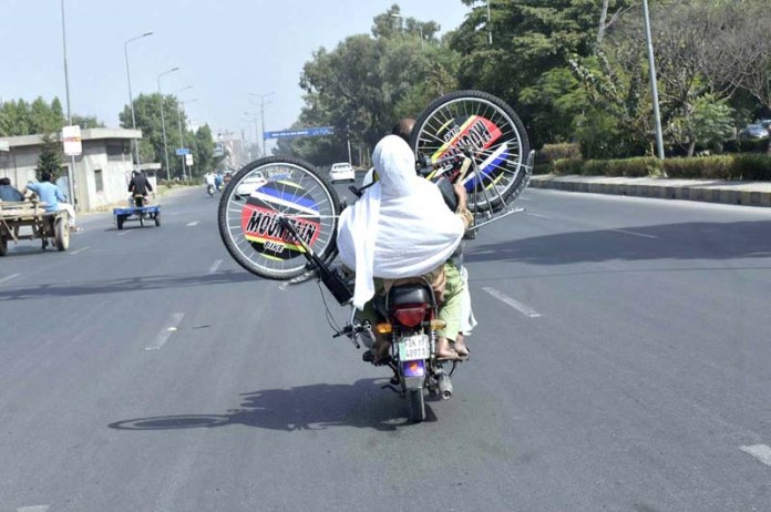 FAISALABAD: October 19 - A pillion rider woman carrying bicycle in a risky way on motorcycle which may cause any untoward incident. APP photo by Muhammad Waseem