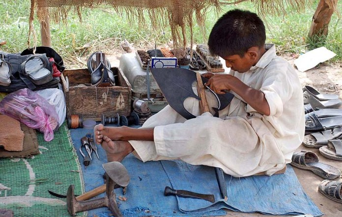 SARGODHA: October 20 - A young cobbler busy in his work at his roadside setup along Selawali Road. APP photo by Hassan Mahmood