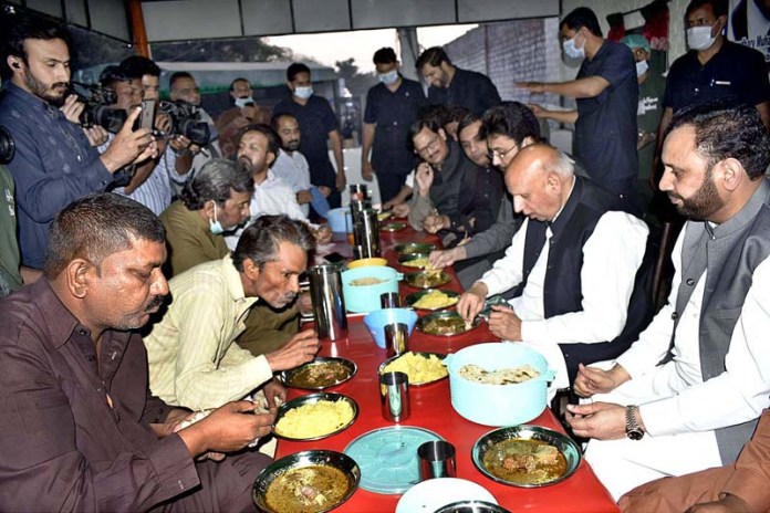 FAISALABAD: October 31 - Governor Punjab Ch Muhammad Sarwar is sharing food with people after inaugurating Langar Khana established by Sylani Welfare Trust at City Terminal near GTS Chowk for free food to the needy people. APP photo by Muhammad Waseem