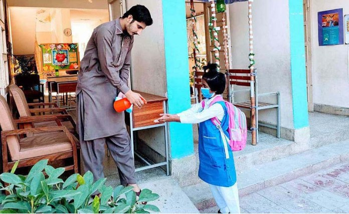 ISLAMABAD: October 17 – A staffer sprays sanitizer on a student's hands as safety measures against the COVID-19 pandemic at IMCG G-11 in the federal capital. APP photo by Saleem Rana