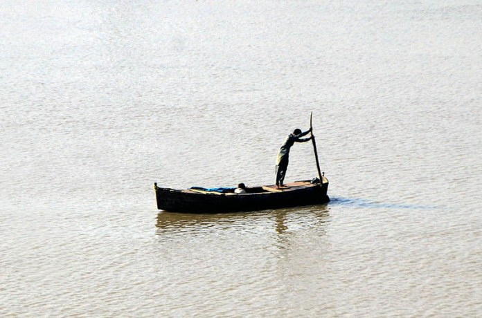 HYDERABAD: October 28 – Fisherman busy in fishing on the boat in Indus River. APP photo by Farhan Khan