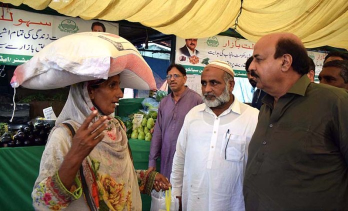 SIALKOT: October 20 - Minister for Special Education Punjab Ch. Muhammad Akhlaq talking to a woman customer about Sahulat Bazaar. APP photo by Muhammad Munir Butt
