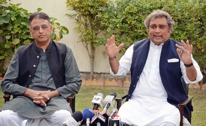 KARACHI: October 18 - Federal Minister for Maritime Affairs Ali Haider Zaidi and Federal Minister for Planning and Development Asad Umar jointly addressing a press conference. APP photo by M Saeed Qureshi