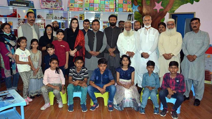 FAISALABAD: October 20 - Advisor to CM Punjab for Tourism and Horticulture Asif Mehmood in a group photo with children after inauguration of Children Library at Jinnah Garden. APP photo by Tasawar Abbas