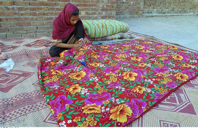 CHINIOT: October 20 - A girl busy in stitching quilt as demand during winter season. APP photo by Muhammad Ali