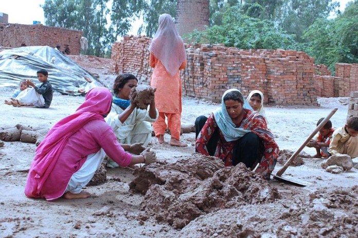SARGODHA: October 05 - Women busy in ready clay for bricks at Jhang Road. APP photo by Hassan Mahmood