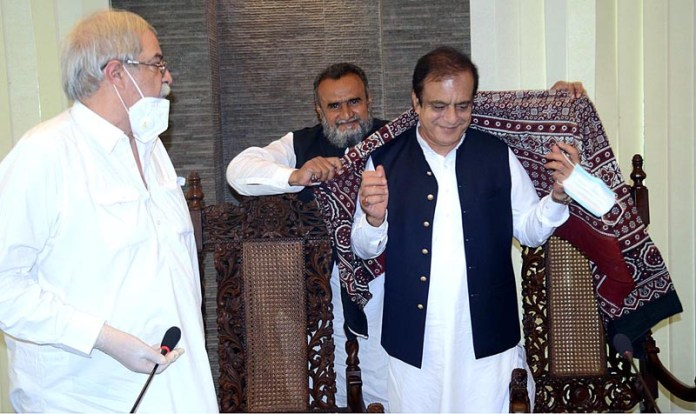 KARACHI: October 07 - Federal Minister for Information and Broadcasting Senator Shibli Faraz receiving traditional Sindhi Ajrak during meeting with All Pakistan Newspapers Society (APNS) members. APP Photo by Abbas Mehdi
