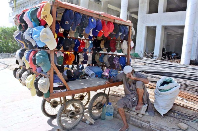KARACHI: October 04 - A road side vendor displayed caps for sell on his hand cart to attract customer in Saddar area. APP photo by M Saeed Qureshi