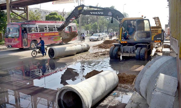 KARACHI: October 22 – Workers are busy in repairing of sewerage line with the help of heavy machinery at Shahrah-e-Pakistan Naseerabad area. APP photo by Syed Abbas Mehdi