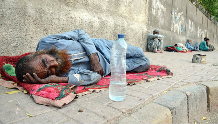 KARACHI: October 16 - An aged labourer is in deep sleep on footpath as a bottle of drinking water is put beside him in the hot weather. APP photo by Syed Abbas Mehdi