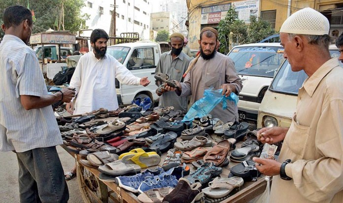 KARACHI: October 22 – People purchasing shoes from a push cart setup of a vendor along the roadside. APP photo M. Saeed Qureshi