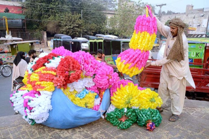 LAHORE: October 29 - Vendors busy in displaying different decorative stuff to attract the customer at his roadside setup. APP photo by Ashraf Ch