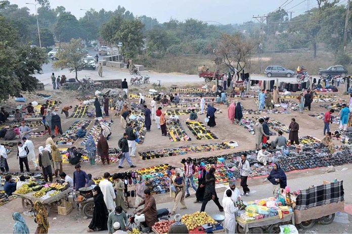 ISLAMABAD: November 10 – People busy in selecting and purchasing second hand shoes displayed by vendors in Federal Capital. APP photo by Saeed-ul-Mulk