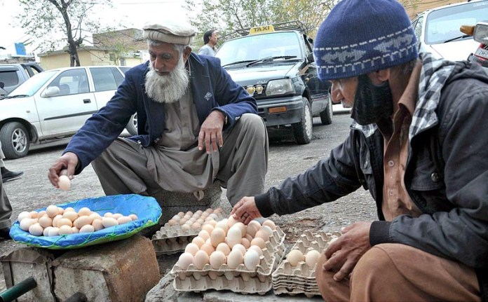 Vendors displaying and arranging eggs to attract the customers in a local market