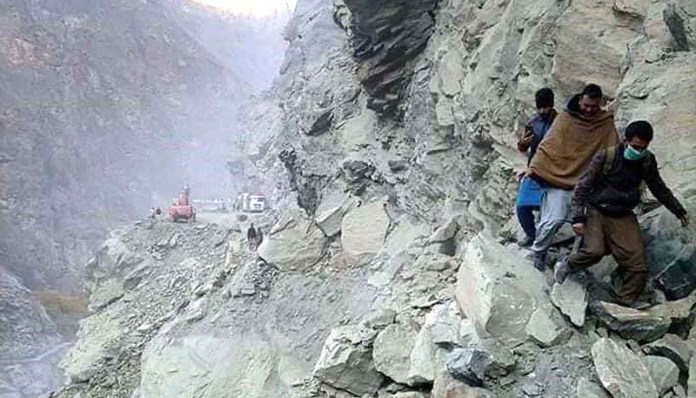 GILGIT: November 07 - People crossing the blocked road in a risky way at Shingus area. APP Photo by Ashraf Hussain