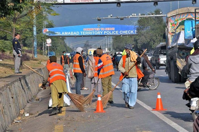 CDA sanitary workers busy in cleaning the Expressway after Tehreek-e-Labaik Pakistan sit in near Faizabad Interchange