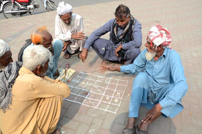 LAHORE: November 06 - A group of people playing traditional game on a footpath. APP photo by Ashraf Ch