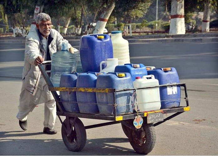 An elderly person pushing handcart loaded with water bottles after filling from water pumps installed at Rakh Branch Canal to supply it to various houses