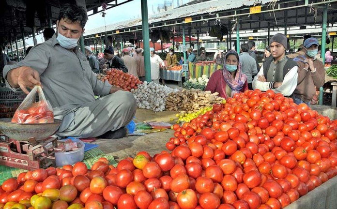 A stall holder displaying tomatoes and other stuff to attract the customers at weekly Sunday Bazaar
