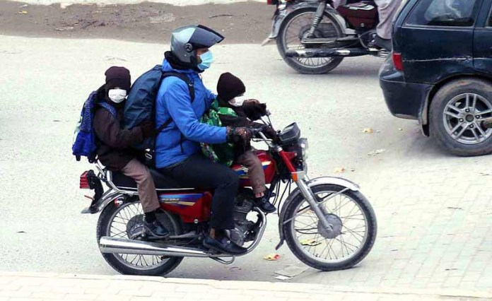 A motorcyclist along with his children wearing masks to protect from COVID-19