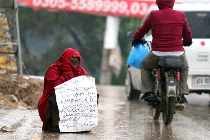 A female beggar sitting on the road asking for mercy during rain that experienced in twin cities