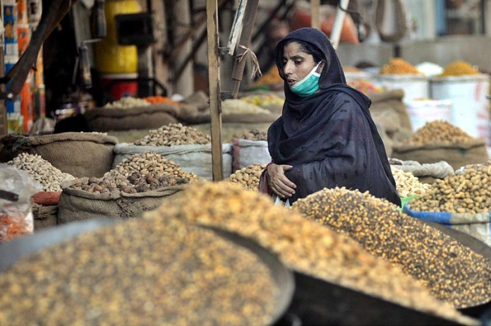 RAWALPINDI: November 04 – A woman purchasing dry fruits from vendor in a local market. APP photo by Irfan Mahmood