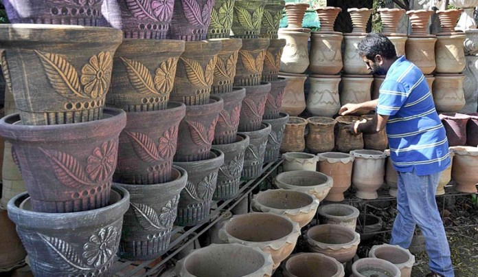 A worker displaying and arranging plant pots to attract the customers