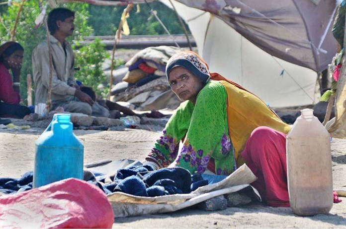HYDERABAD: Gypsy woman busy in washing clothes outside hut on the greenbelt. APP photo by Farhan Khan