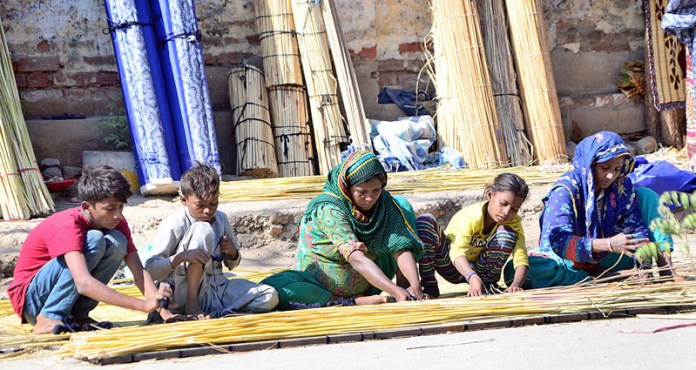 A labourer family preparing traditional curtains (chicks) at their roadside workplace