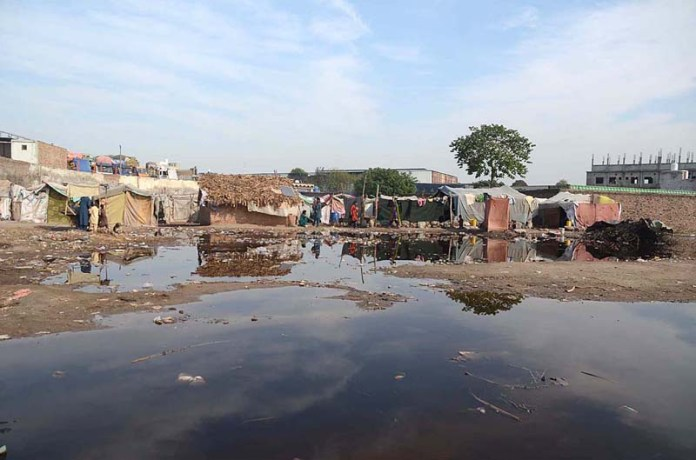 A view of rain water accumulated in front of makeshift houses near Ring Road