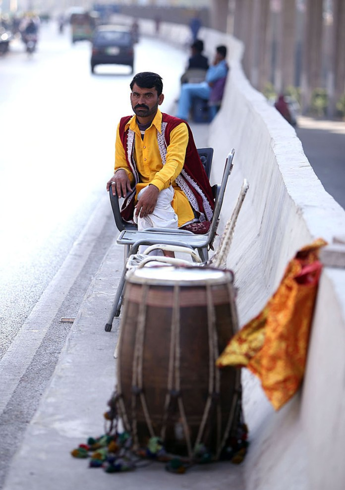 RAWALPINDI: November 06 – A traditional drummer waiting for job along the roadside at Marrir Chowk to earn for livelihood. APP photo by Abid Zia