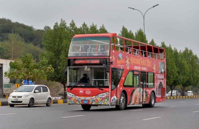 Tourists enjoying a ride on double dacker bus while visiting twin cities landmarks by PTDC
