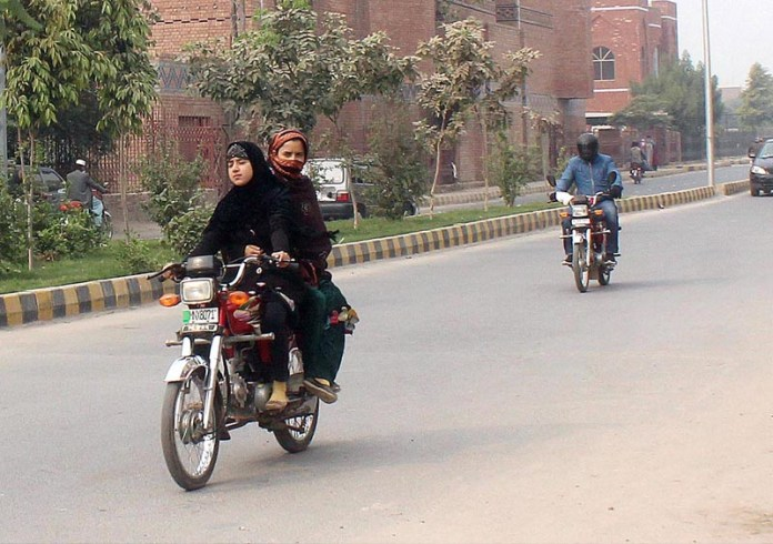 A girl riding motorcycle heading towards her destination