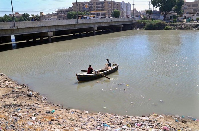 HYDERABAD: November 04 – Fishermen busy in catching fish on boat at Phuleli Canal. APP photo by Akram Ali