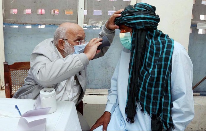 Doctor examining a patient during free medical camp established by Pakistan Navy at Keti Bander