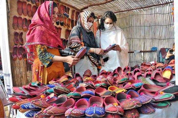 """ISLAMABAD: November 08 – Visitors taking keen interest in traditional shoes Khusa on displayed at a stall at Folk Festival of Pakistan """"LOK MELA"""" at Lok Virsa Shakarparian. APP photo by Saeed-ul-Mulk"""