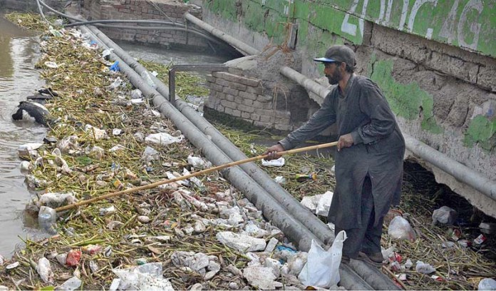 A gypy collecting valuables from waste material floating on surface of water at Rakh Branch Canal