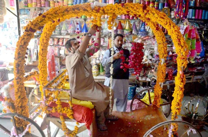 "Vendor busy in decorating horse cart ""Bhagee"" to attract the customers to be used during wedding ceremony (Mehndi function)"
