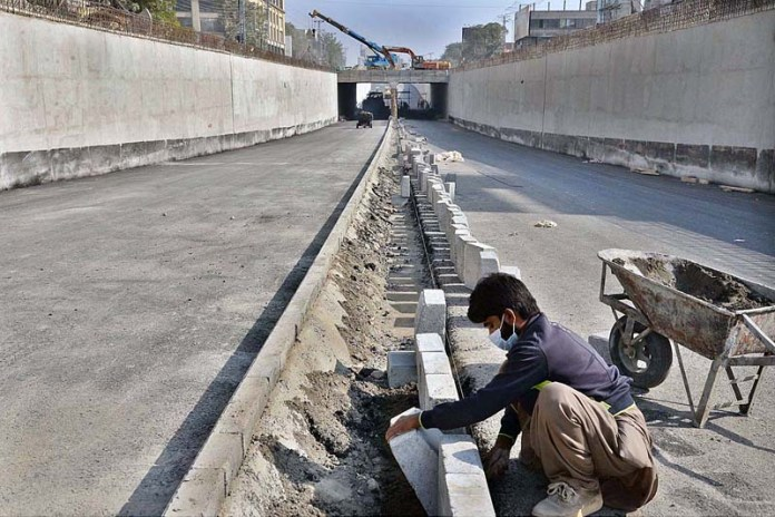 LAHORE: November 04 – Labourers busy in construction work of Firdous Market Underpass during development work in Provincial Capital. APP photo by Amir Khan