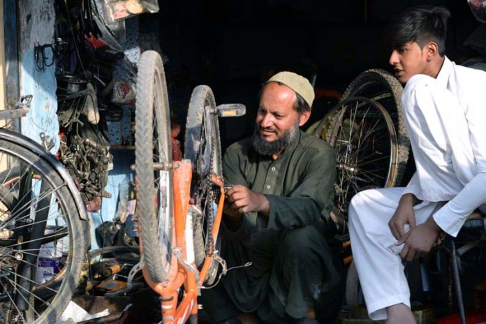 ISLAMABAD: November 09 – A mechanic busy in repairing a bicycle at his roadside workplace. APP photo by Irshad Sehikh