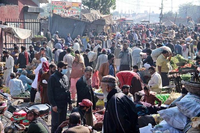 People purchasing vegetables from vendors at Sabzi Mandi