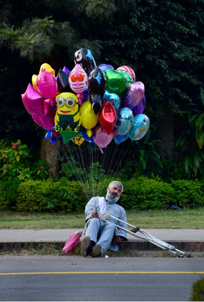 ISLAMABAD: November 08 – A handicap waiting for customers at roadside to sell balloon for livelihood in the federal capital. APP photo by Irshad Sheikh