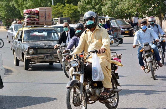 KARACHI: November 10 - Motorcyclists on the way wearing safety masks as the government taken strict precautionary measures to control the corona virus pandemic if anyone seen without wearing a mask on the road have a fine of Rs 500. APP Photo by Saeed Qureshi
