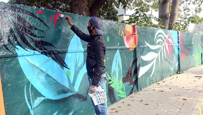 A painter giving final touches during painting on wall